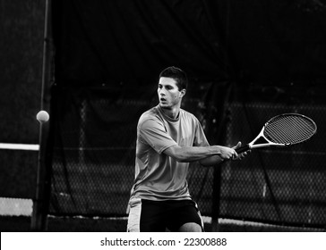 Athletic young man (in twenties) playing tennis
