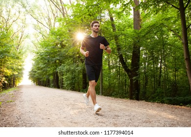 Athletic young man running in the nature. portrait of male runner training for marathon. Healthy lifestyle