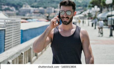 Athletic young man at the seaside calling on cell phone while walking and looking at the sea