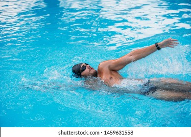 Athletic Young man swimming on Backstroke style. Swimming competition.