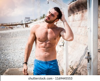 Athletic young man taking a shower on the beach in Nice, France on the French Riviera