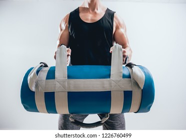 Athletic young man training with sandbags at gray background. Crossfit center. Fitness concept.