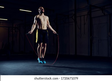 Athletische junge Mann Ausbildung mit Skip-Seil. Cardio-Training mit minimalem Equipment