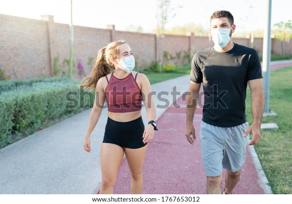 Athletic young man and woman wearing face masks while walking in park