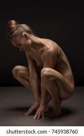 Athletic young sensual nude woman with ideal natural body stretches on black background. Concept of a healthy lifestyle, diet and sport.