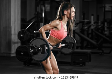 athletic young sexy fitness girl training with barbell in the gym