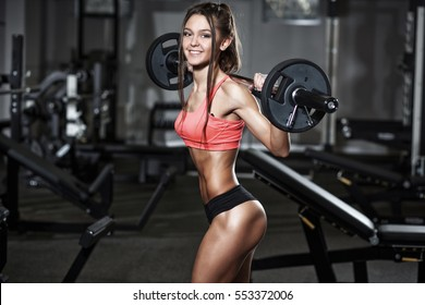 athletic young sexy smiling girl training with barbell in the gym