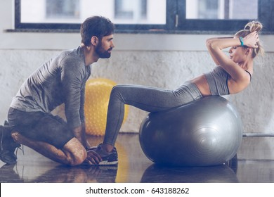 athletic young sportswoman doing abs on fitness ball at the gym, fitness couple gym concept