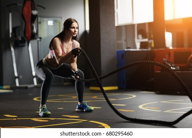 Athletic young woman doing crossfit exercises with a rope