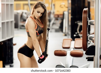 Athletic young woman doing exercise on the triceps in the crossover in the gym.