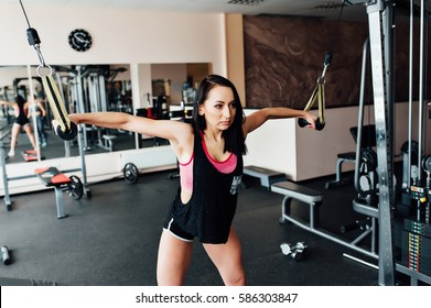 Athletic young woman doing exercises on the simulator for the upper muscle groups