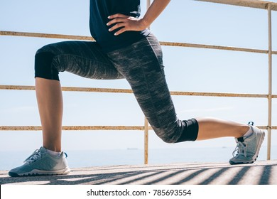 Athletic young woman doing lunges in the morning on the beach