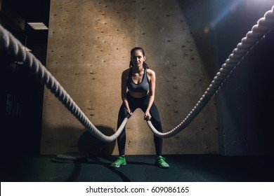 Athletic young woman doing some crossfit exercises with a rope outdoor