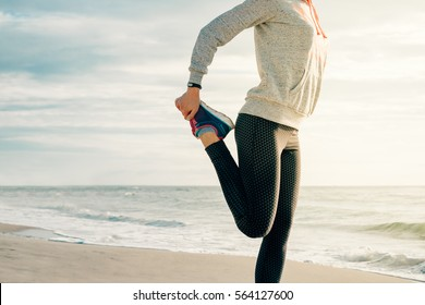 Athletic young woman doing sport exercises on the beach in the morning. The concept of a healthy lifestyle.