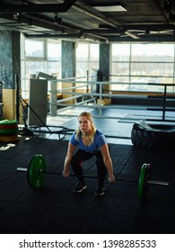 Athletic young woman doing squat preparing to lift barbell with weights during gym workout