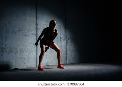 Athletic young woman exercising with kettlebell in dark garage on concrete background