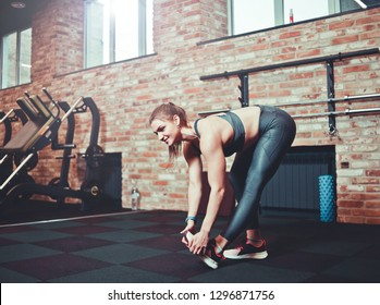 Athletic young woman with perfect body in sportswear does stretches for legs in gym. Warm up before training