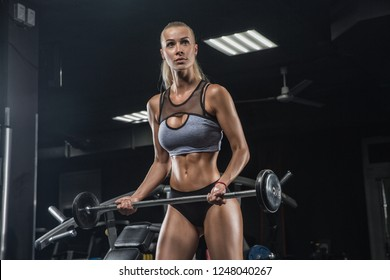 Athletic young woman posing and exercising fitness workout with weights in the gym on diet