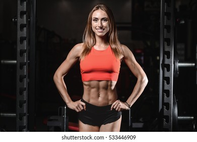 Athletic young woman posing and exercising fitness workout with weights in the gym lifestyle portrait, caucasian model fitness and bodybuilding