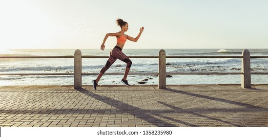 Athletic young woman running on seaside promenade. Side view of female runner sprinting outdoors.
