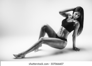 Athletic young woman showing muscles. Studio shot.