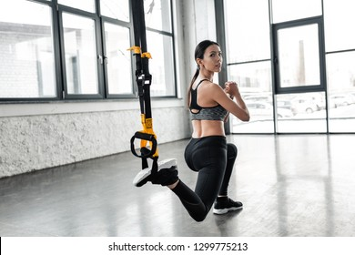 athletic young woman in sportswear training with resistance bands and looking at camera in gym