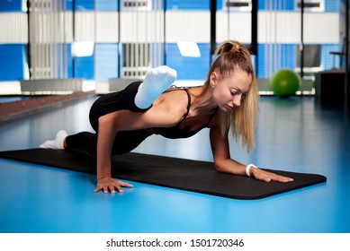 Athletic young woman is training in the gym.
