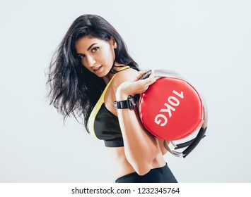 Athletic young woman training with sandbags at gray background. Crossfit center. Fitness concept.