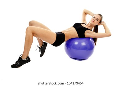Athletic young woman working out abs with the fitball