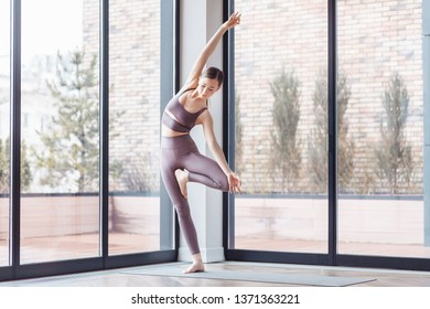 Athletic young woman yoga instructor doing vrikshasana standing near the large windows of the gym. Concepts of flatfoot correction and poor posture