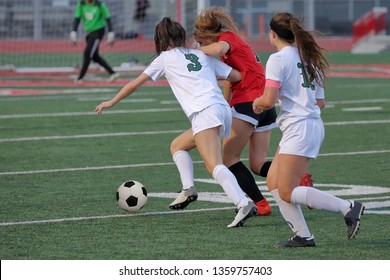 Athletic young women playing in a competitive university interscholastic league high school soccer match playoff game