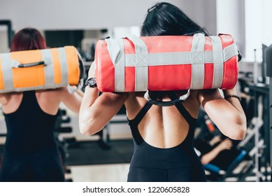 Athletic young women training with sandbags at gray background. Crossfit center. Fitness concept.