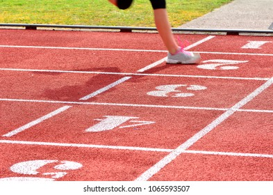 Athletics competition on a red track; motion effect.