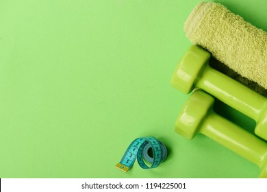 Athletics and weight loss concept. Tape measure in cyan color by barbells, copy space. Sports and healthy regime equipment. Dumbbells in green color, twisted measure tape and towel on green background