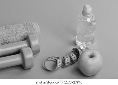 Athletics and weightloss concept. Dumbbells in bright green color, water bottle, measure tape, towel and fruit on green background. Barbells near juicy green apple. Sports and healthy regime equipment