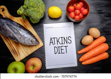 Atkins Diet on chalkboard, health conceptual. Healthy fresh food fish, lemon, tomatoes, apple, carrot and broccoli.
