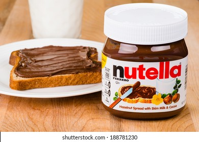ATLANTA - APRIL 23, 2014: Jar of Nutella, toast with Nutella spread and milk to drink.