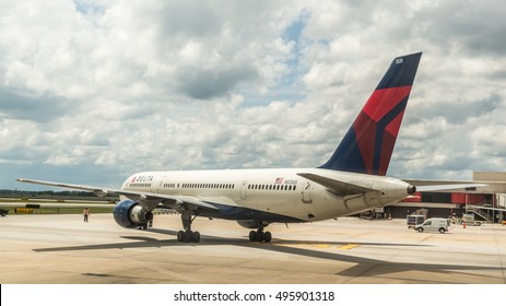 Atlanta - Aug 30: A ground technician at Atlanta International Airport directs a delta air plane out of its departure gate for takeoff on Aug 30, 2014 in Atlanta, Georgia.