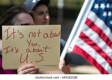 """ATLANTA, GA - APRIL 15:  A woman holds sign that says """"It's not about you, it's about U.S."""" as she listens to speakers at the Atlanta Tax March, on April 15, 2017 in Atlanta, GA."""