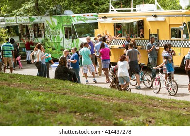 ATLANTA, GA - APRIL 16:  A large crowd of people buy meals from food trucks lined up in Grant Park at the Food-o-rama festival on April 16, 2016 in Atlanta, GA.