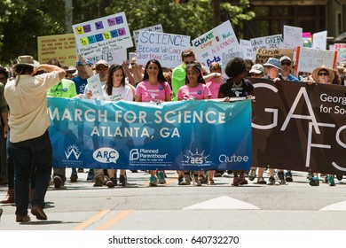 ATLANTA, GA - APRIL 22:  People carry the Atlanta March for Science banner, as thousands line up behind to begin the march at Candler Park on Earth Day on April 22, 2017 in Atlanta, GA.