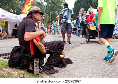 ATLANTA, GA - AUGUST 16:  A man strums a bass guitar for tips while sitting on the curb at the Piedmont Park Arts Festival on August 16, 2014 in Atlanta, GA.