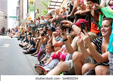 ATLANTA, GA - AUGUST 31:  A huge crowd of spectators lines Peachtree Street in downtown Atlanta, and takes pictures as the annual Dragon Con parade passes by on August 31, 2013 in Atlanta, GA.