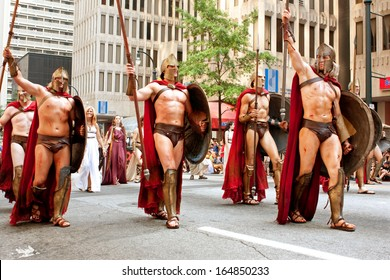 """ATLANTA, GA - AUGUST 31:  Several men representing Spartan warriors from the movie """"300"""" salute the crowd while walking in the annual Dragon Con parade, on August 31, 2013 in Atlanta, GA."""