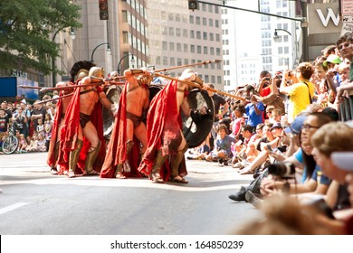 """ATLANTA, GA - AUGUST 31:  Several men representing Spartan warriors from the movie """"300"""" go into attack formation as they participate in the Dragon Con parade, on August 31, 2013 in Atlanta, GA."""