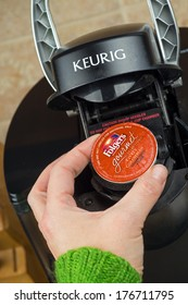 ATLANTA, GA -- FEB 14, 2014: Close-up of woman inserting single-serve K-cup Foldger's coffee into a Keurig coffee maker.