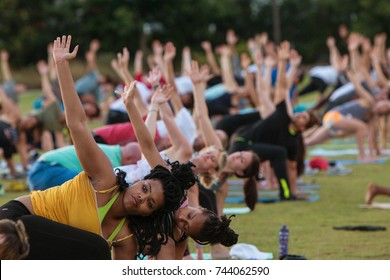 ATLANTA, GA - JULY 2:  Dozens of people do the triangle yoga pose as they take part in a free group yoga class at the Old Fourth Ward Park on July 2, 2017 in Atlanta, GA.