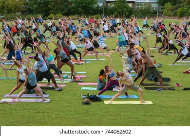ATLANTA, GA - JULY 2:  Dozens of people stretch doing a yoga pose as they take part in a free group yoga class at the Old Fourth Ward Park on July 2, 2017 in Atlanta, GA.