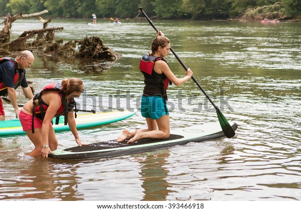 ATLANTA, GA - JULY 25:  A young woman kneels on a paddleboard as she gets a push into the Chattahoochee River on a hot summer day on July 25, 2015 in Atlanta, GA.
