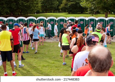 ATLANTA, GA - JULY 4:  Exhausted runners wait in long lines to use a Johnny On The Spot portable toilet, after just completing the Peachtree Road Race 10K on July 4, 2014 in Atlanta, GA.